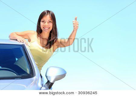 Coche. Mujer conductora feliz sonriendo mostrando pulgar arriba saliendo de ventanilla en el cielo de verano azul