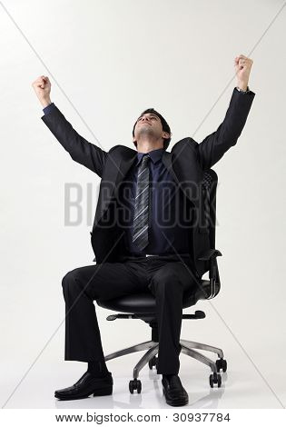 Business man sitting  on office chair with arm raised