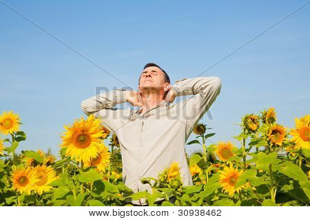 older man enjoying breathing deep in parc field