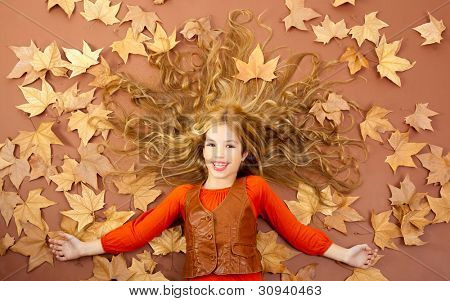 autumn fall little blond girl on dried tree leaves background and long spread hair