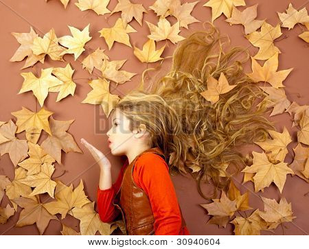autumn fall little blond girl on dried tree leaves blowing wind with lips