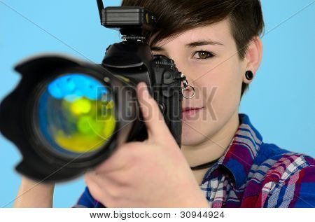 young photographer with digital SLR camera on blue background