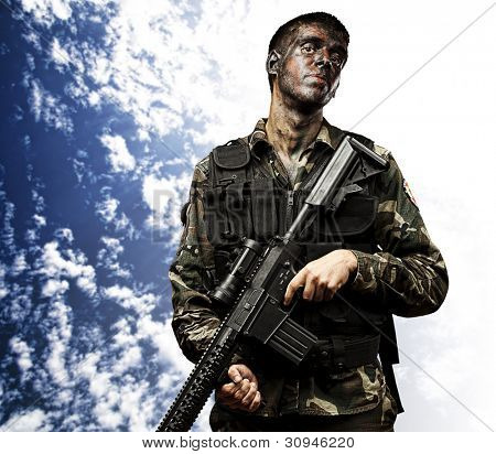 portrait of young soldier holding rifle against a blue sky background