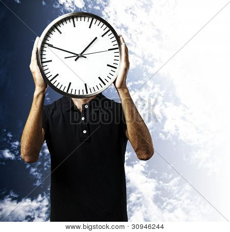 portrait of a young man holding a clock with his hands against a cloudy sky background