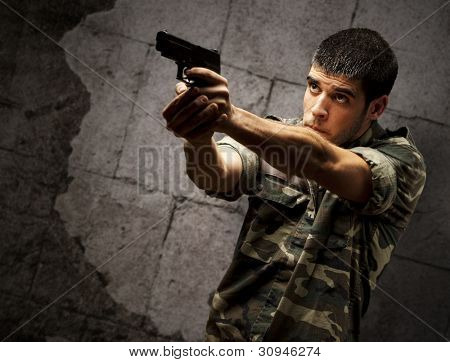 portrait of a young soldier aiming with a pistol against a grunge brick wall