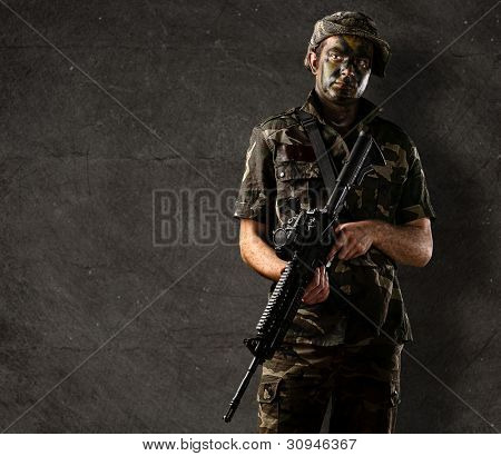portrait of a young soldier with jungle camouflage holding a rifle against a grunge wall