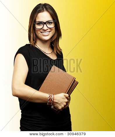 portrait of a young student with glasses holding an old book over a yellow background