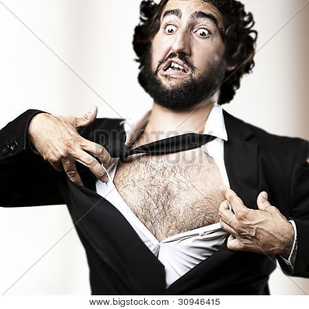 business man with courage and superman concept tearing off his shirt against an abstract background