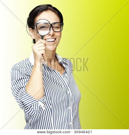 portrait of a woman looking through a magnifying glass against a green background