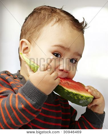 portrait of a handsome kid bitting a watermelon piece indoor