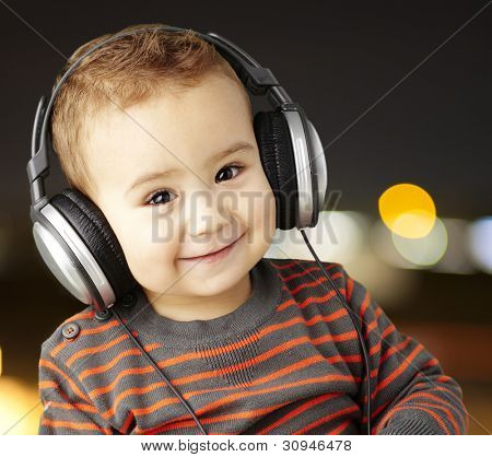 portrait of a handsome kid listening to music and smiling at a city night background