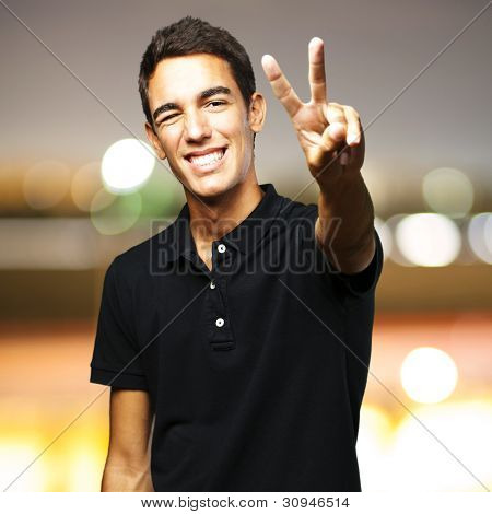 portrait of a young man smiling and doing a good symbol against a city by night