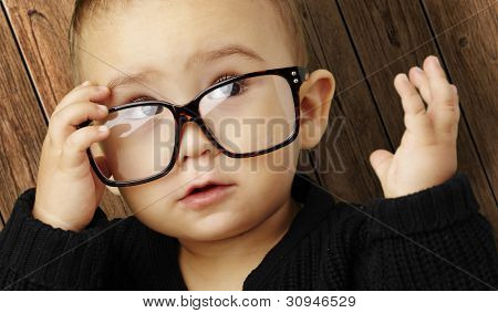 portrait of a kid wearing glasses against a wooden background