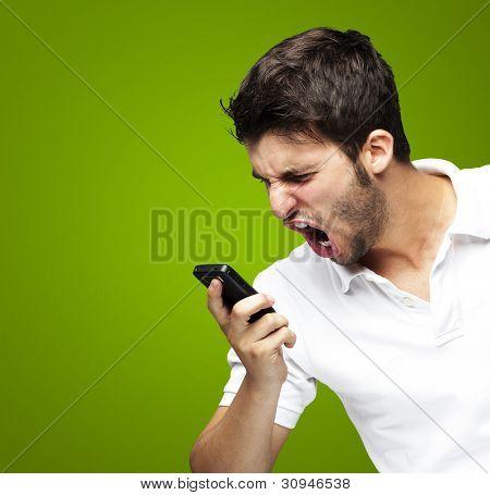 Retrato de un grito de angry young man usando un móvil sobre un fondo verde