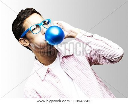 portrait of a young man with glasses inflating a blue balloon against a white background