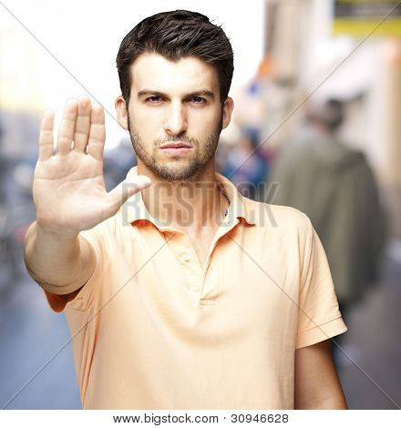 portrait of a comely young man doing a stop symbol at a crowded street
