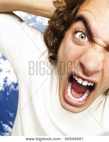 portrait of a furious young man shouting against a cloudy sky background