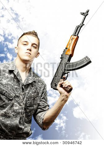portrait of a young soldier holding a rifle wearing a urban camouflage against a cloudy sky background