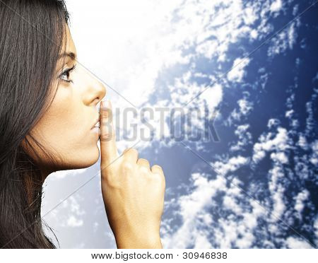 portrait of a young woman doing a silence sign against a cloudy sky background