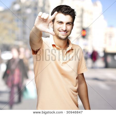 portrait of a handsome man doing a good symbol at a crowded city