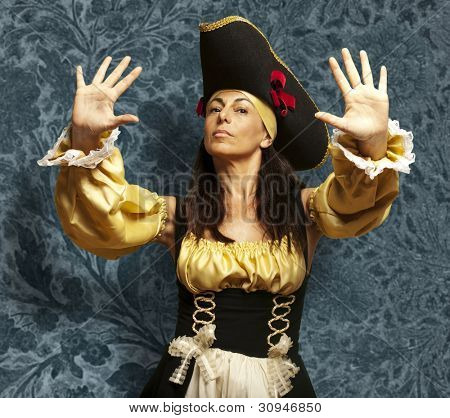portrait of a pirate woman gesturing a stop against a vintage background
