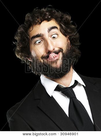 portrait of a young business man showing the tongue over a black background