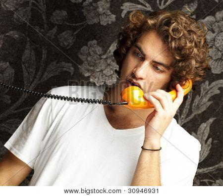 retrato de um jovem falando no telefone vintage contra uma parede vintage