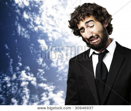 portrait of a young business man with a suit crying against a blue sky background