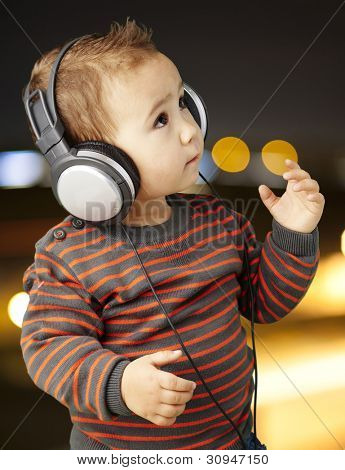 portrait of an adorable kid with headphones listening to music at a city background