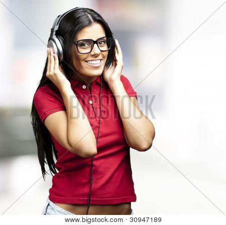 portrait of a young woman listening to music against an abstract background