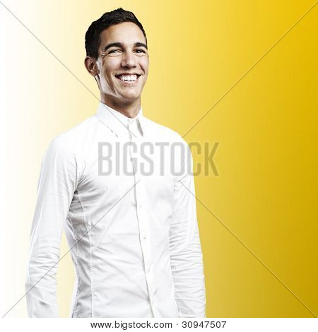 portrait of a young man smiling against a yellow background