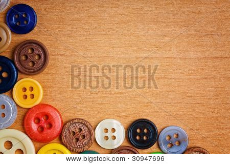 Colorful sewing buttons creating a frame on a wooden background with space for text