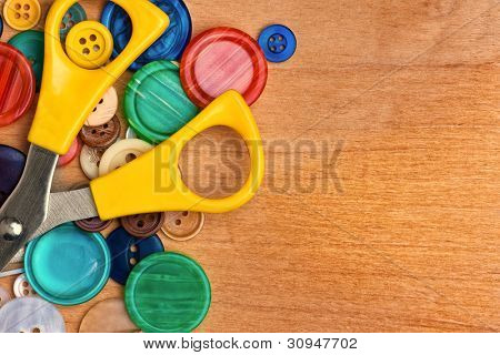 Sewing buttons and scissors on a wooden background with space for text