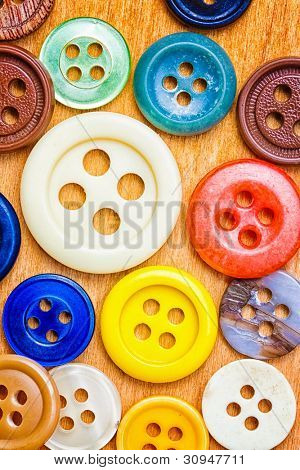 Assorted collection of colorful sewing buttons on a wooden background