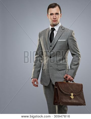 Businessman with a briefcase on grey background.