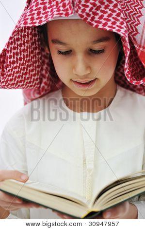 Muslim Arabic little boy reading Qoran