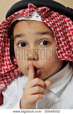 Cute arabian kid asking for silence, secret