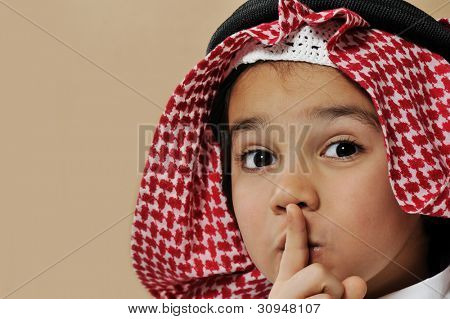 Cute arabian kid saying psst, silence please