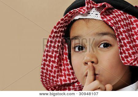 Cute arabian kid saying psst, silence please
