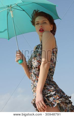 Sexy young woman posing with an umbrella.