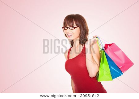 Smiling woman wearing glasses walking with three brightly coloured shopping bags slung over her shoulder