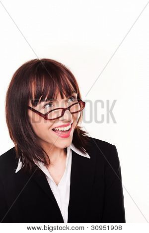 Laughing businesswoman looking up over the top of her glasses or spectacles into blank copyspace above her head