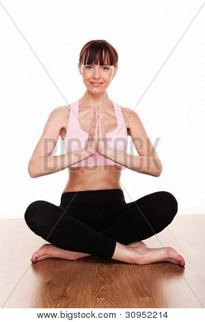 Woman practising yoga sitting in the lotus position with her hands clasped in prayer