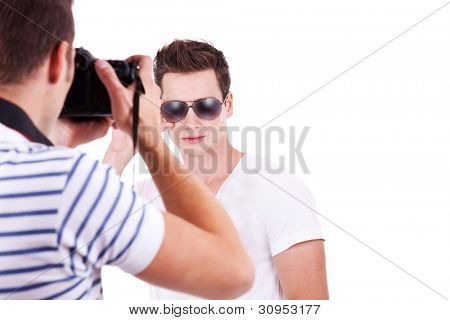 professional male photographer taking a picture of his male model on white background