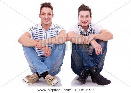amigos de dois homens olhando muito feliz, sentado ao lado do outro em fundo branco