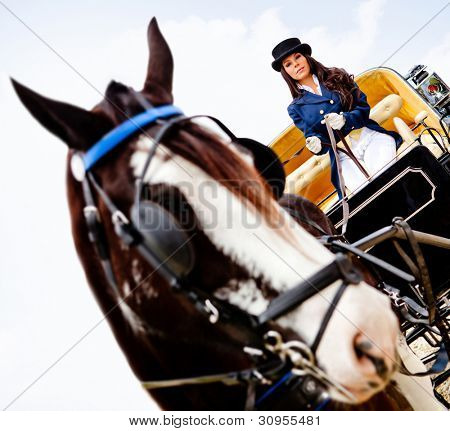 Beautiful woman in an outfit driving a horse carriage