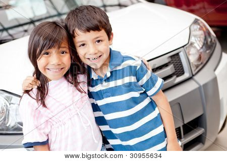 Two kids at the dealer buying a family car