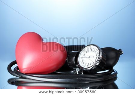 Black tonometer and heart on blue background
