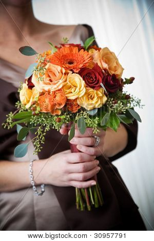 A brides wedding bouquet of flowers being held in her hands.