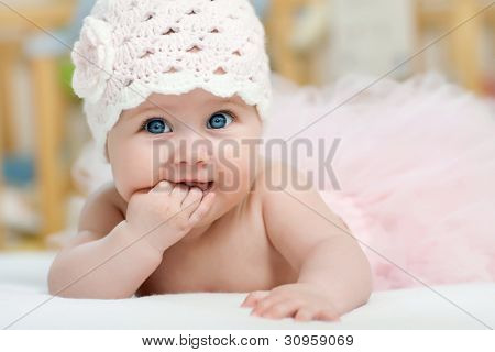 Charming child. Little girl with hat lying on her stomach and sucks fingers